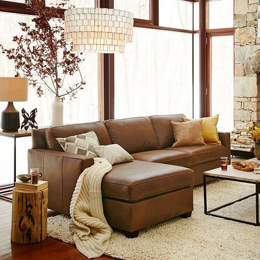 living room, white rug, brown leather sofa, neutral colored exposed wall, side table, coffee table