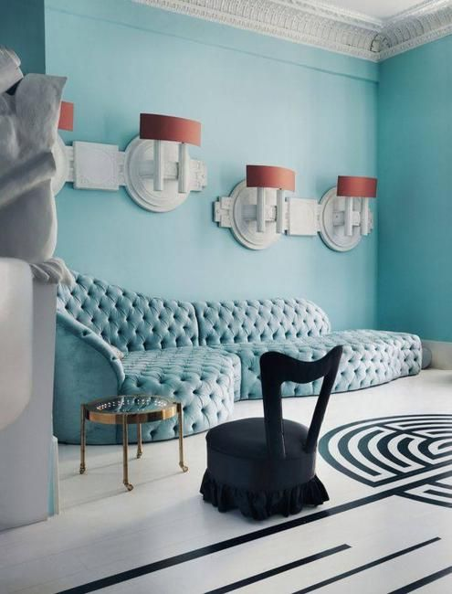 living room, white wall, black chair, golden side table, blue wall blue tufted sofa