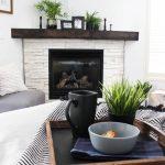Living Room, White Wall, White Brick Corner Fireplace, Black Wooden Shelves, Grey Chair