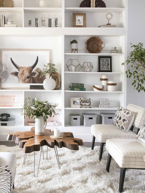living room, white wall, white wooden shelves, white chairs, wooden coffee table, plants, wooden floor, white rug