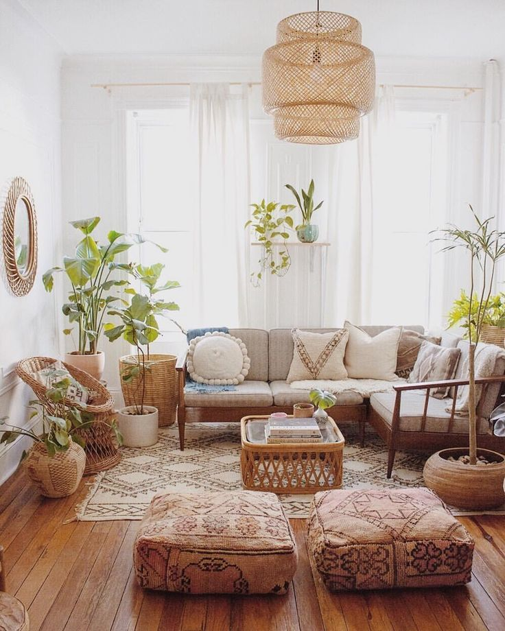 living room, wooden floor, brown patterned rug, brown floor pillows, wooden sofa, white cushion, rattan chairs, rattan plant pot, rattan pendant, white curtain