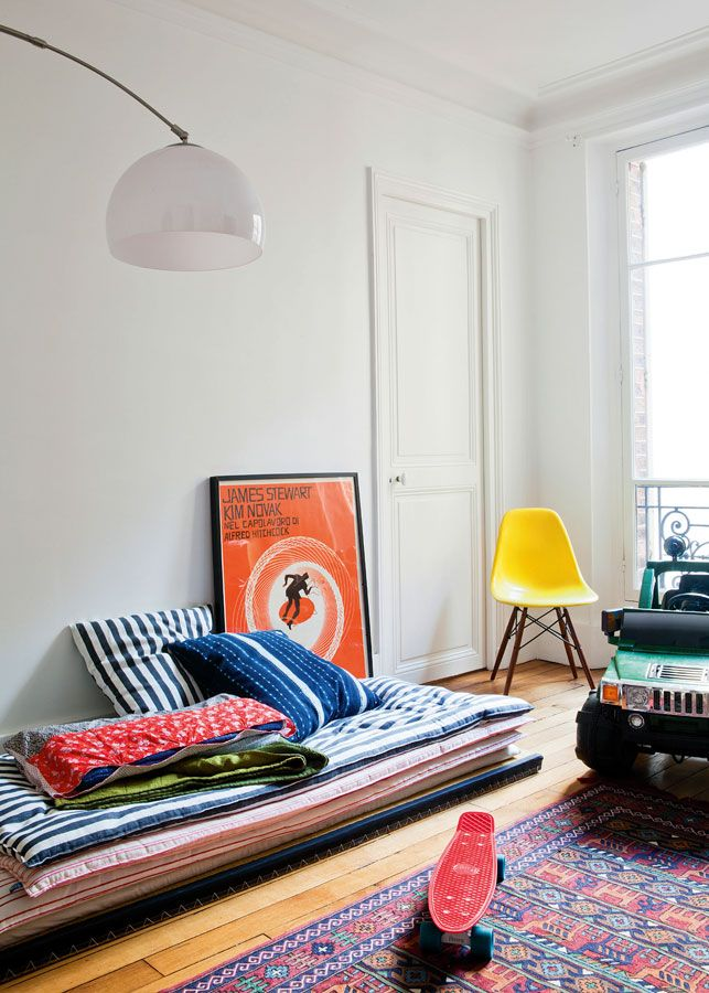 living room, wooden floor, colorful patterned rug, stack of patterned matress, yellow chair,