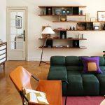 Living Room, Wooden Floor, Dark Green Sofa, Brown Leather Chair, Wooden Floating Shelves, Floor Lamp