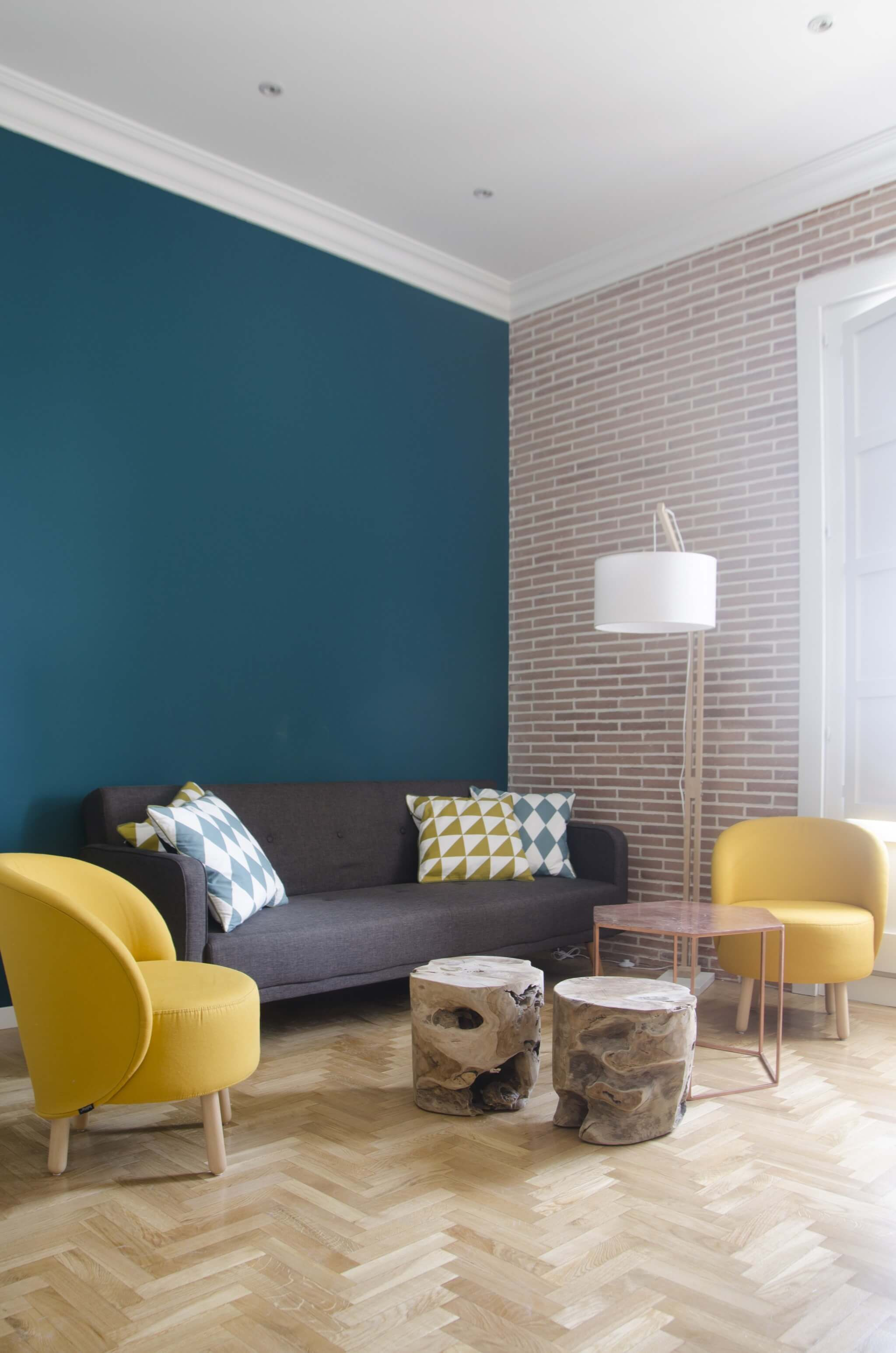 living room, wooden floor, green wall, grey sofa, yellow chairs, wooden slab coffee table, white floor lamp