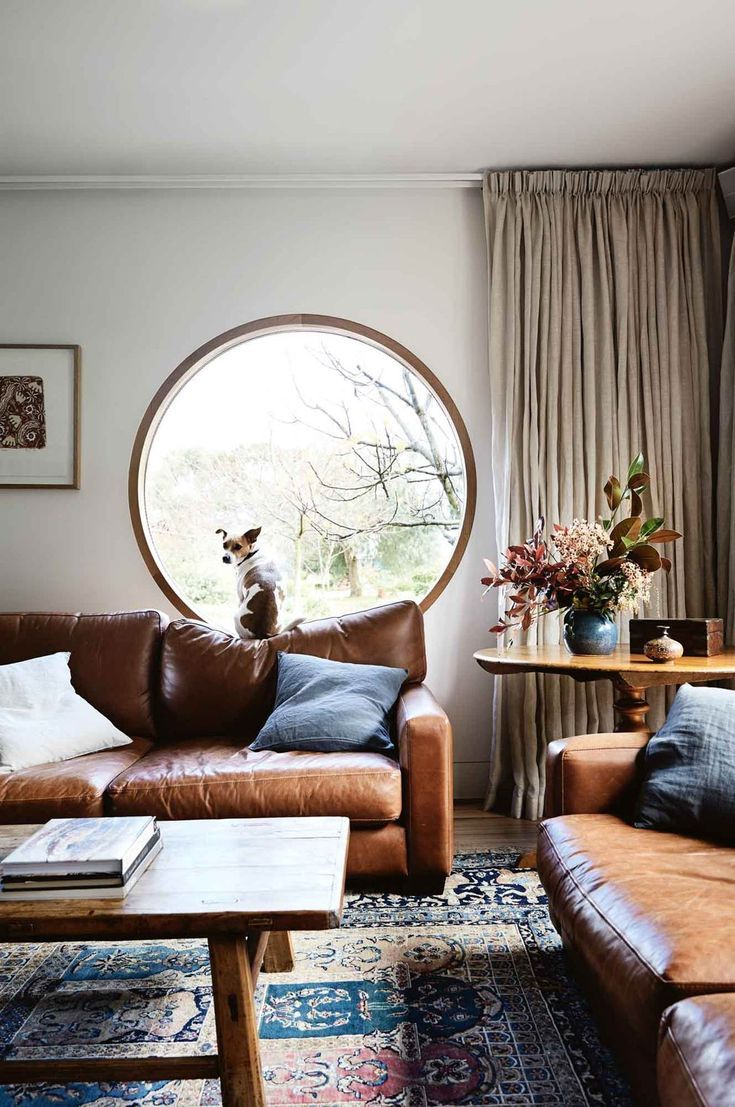 living room, wooden floor, patterned rug, white wall, round window, white currtain, brown leather sofa, wooden coffee table