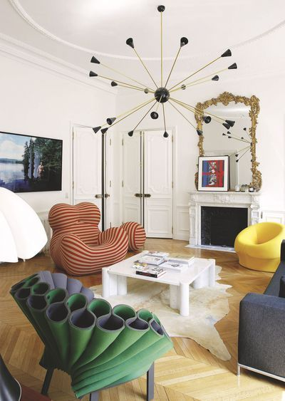 living room, wooden floor, white coffee table, yellow chair, red white striped chair, green purple chair, grey sofa, black modern chandelier, white fireplace