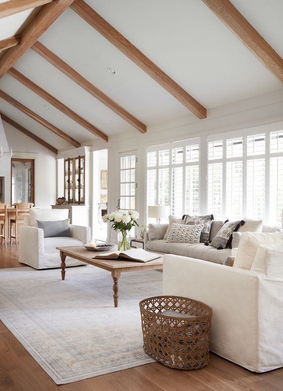living room, wooden floor, white rug, wooden coffee table, white sofa, white chair, whiite wall, wooden beams