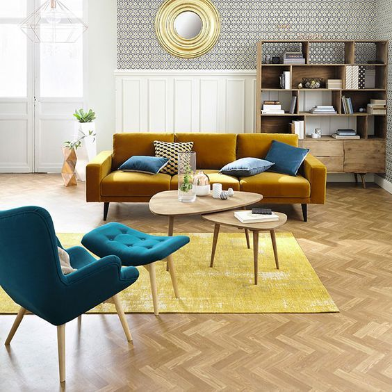 living room, wooden floor, white wainscoting wall, round golden framed mirror, wooden shelves, mustard sofa, green lounge chair and tufted ottoman, yellow rug