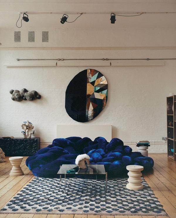 living room, wooden floor, white wall, blue velvet sofa, glass coffee table, patterned rug