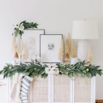 Living Room, Wooden Floor, White Wall, White Cabinet With White Rattan Door, White Table Lamp, Garland With Flowers