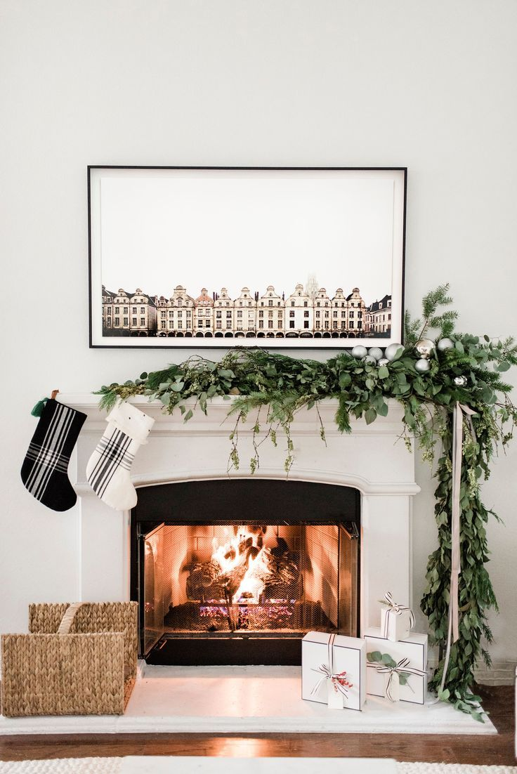 living room, wooden floor, white wall, white fireplace, garland, rattan box