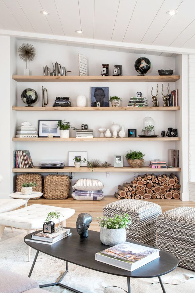 living room, wooden floor, white wall, wooden shelves on nook, rattan basket, white low stools, black wooden coffee table