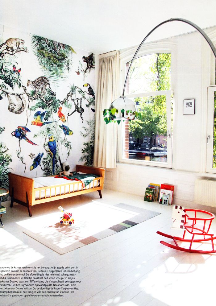 nursery, white wooden floor, white wall, animal wallpaper, woden bed, red wooden rocking toy, silver lamp