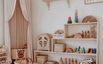nursery, wooden floor, grey rug, white wall, wooden shelves, pink curtain, rattan crib, rattan box