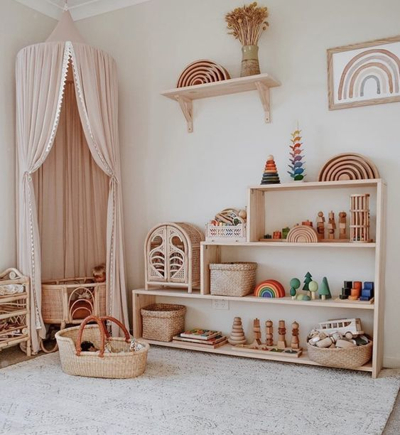 nursery, wooden floor, grey rug, white wall, wooden shelves, pink curtain, rattan crib, rattan box