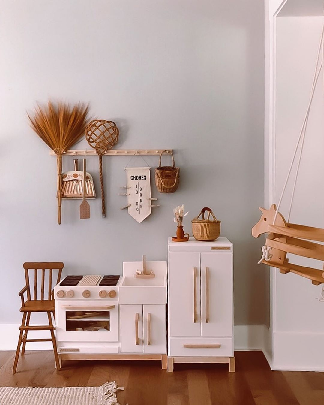 nursery, wooden floor, white wall, white cabinet, white sink, woodne hooks, wooden chair, wooden swing