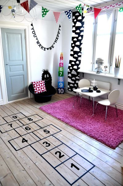 nursery, wooden floor, white wall, white study table and chair, black chair