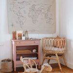 Nursery, Wooden Floor, White Wooden Wall, Rattan Crib, Ratan Toys, Pink Wooden Cabinet, Patterned Rug