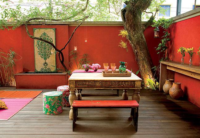 patio, orange wall, wooden floor, wooden table, wooden bench, trees