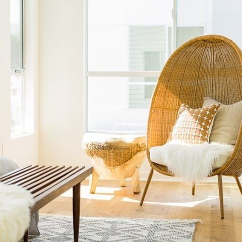 rattan chair in half egg shape, white cushion, wooden side table