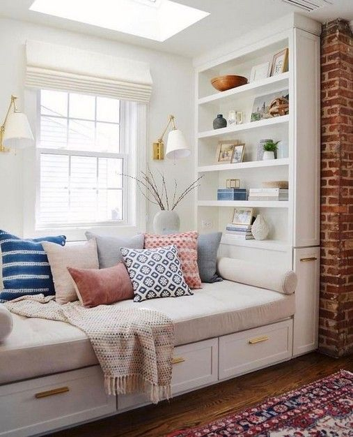 reading nook, white built in bench with drawers, white built in bookshelves, white wall, white sconces, white cushion, glass window ceiling, red brick well