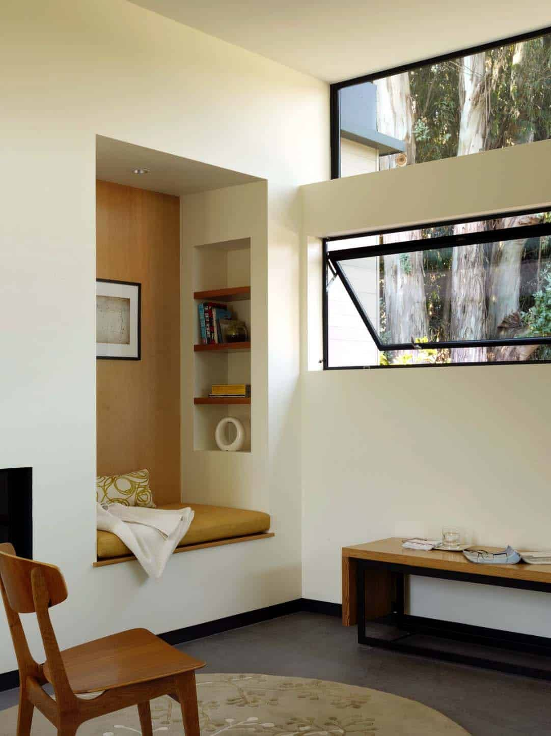 reading nook, white wall, built in shelves, brown cushion, black bench with wooden top, large windows