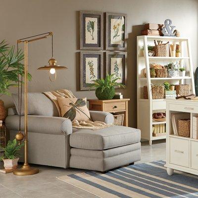 reading spot, off white floor, cream wall, grey lounge chair, golden floor lamp, white shelves, wooden side table