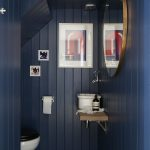 Small Toilet, Blue Wooden Wall, Small Wooden Floating Vanity With White Sink, Round Mirror, Blue White Patterned Floor Tiles