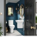 Small Toilet, Blue Wooden Wall, White Patterned Floor, White Toilet, White Floating Sink, Round Mirror With Golden Frame,