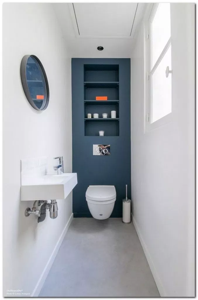 small toilet, grey floor, white wall, blue accent wall, round mirror, indented shelves, white floating toilet, white floating sink