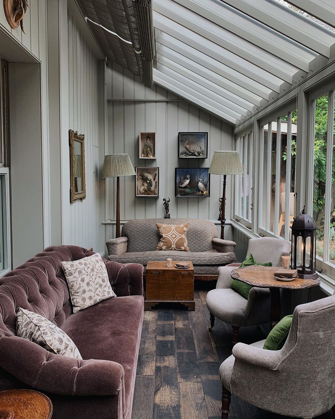 sunroom, black wooden floor, white wooden wall, glass wall, glass window ceiling, purple velvet sofa, grey chairs, wooden side table
