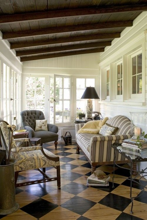 sunroom, brown checkered floor, striped sofa, grey tufted chair, patterned chair, black iron side table with glass top, glass window