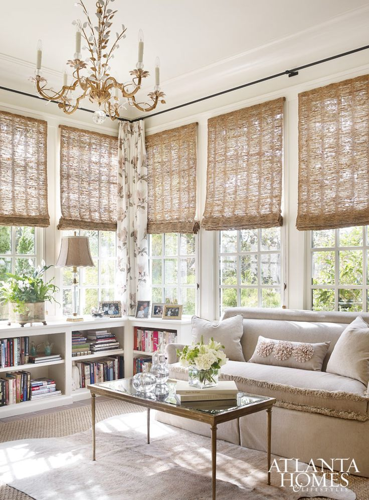 sunroom, brown rug, white shelves, rattan shade, chandelier, brown sofa, golden coffee table with glass top