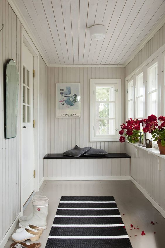 sunroom, white shiplank wall, white built in wooden bench, black wooden bench top, grey seamless floor, glass windows