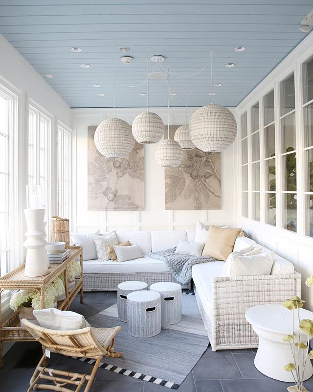 sunroom, white wall with glass, white round pendants, white rattan sofa, white cushion, white rattan stools, rattan chair, rattan consola table