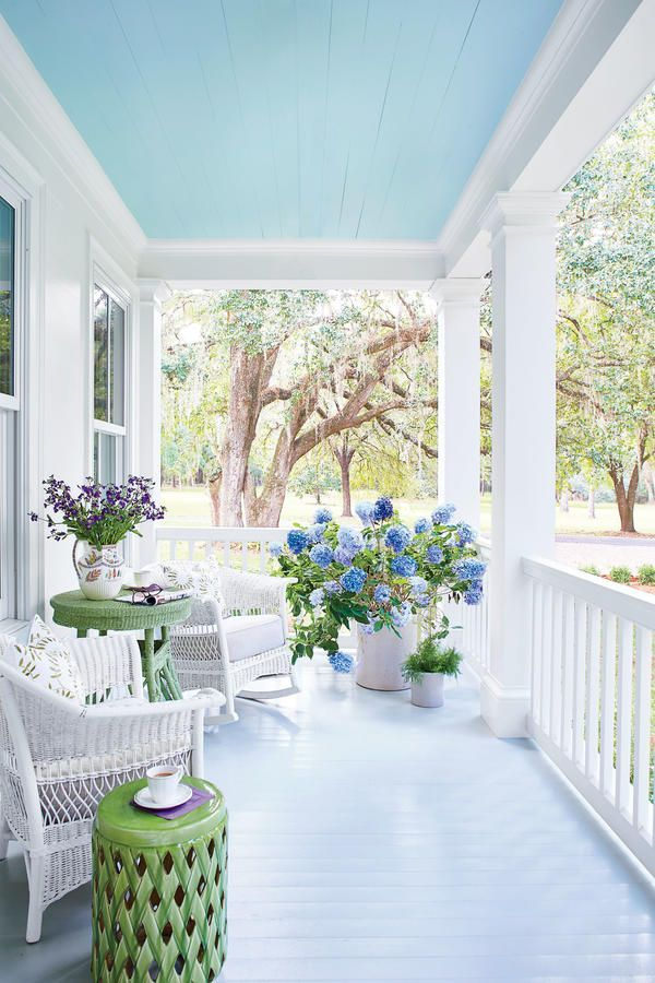 turquoise wooden ceiling, turquoise wooden floor, white wall, white fence, white rattan chairs, green rattan coffee table