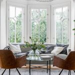Window Bay, White Wall, White Framed Window, White Iron Framed Pendant, Grey Sofa, Brown Leather Chairs, Round Coffee Table, Grey Rug