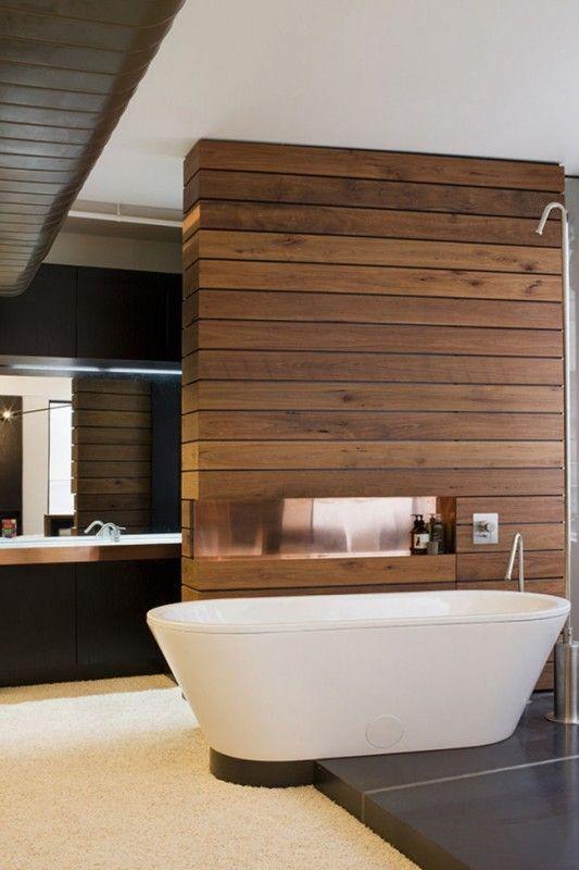 bathroom, black floor, white rug, white tub, wooden partition, black vanity, mirror