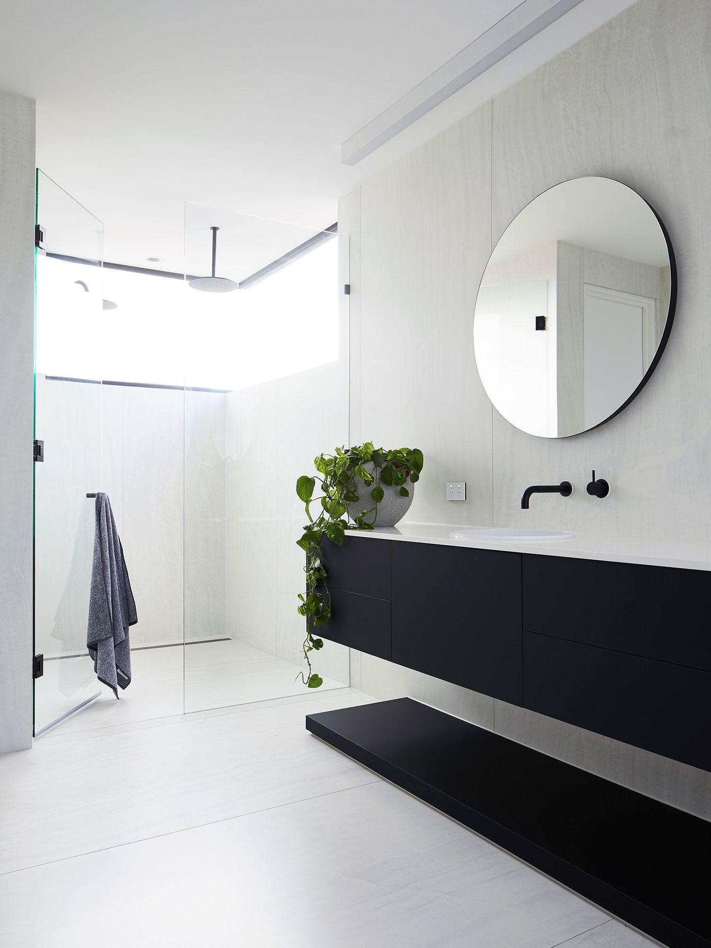 bathroom vanities, black floating cabinet with white top, black floor shelves, round mirror