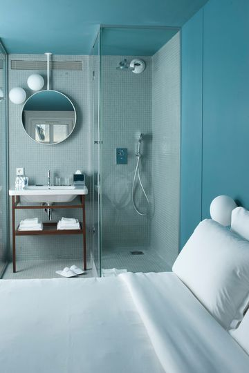 bathroom, white floor, white wall, blue wall, shower closed by glass wall, white sink, vanity table