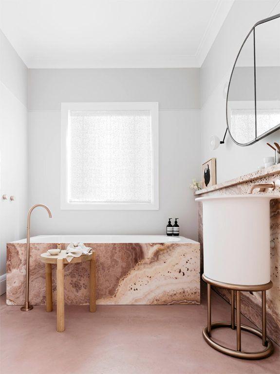 bathroom, white round sink vanity, golden stool, pink marble tub, white wall, round mirror, pink marble shelves