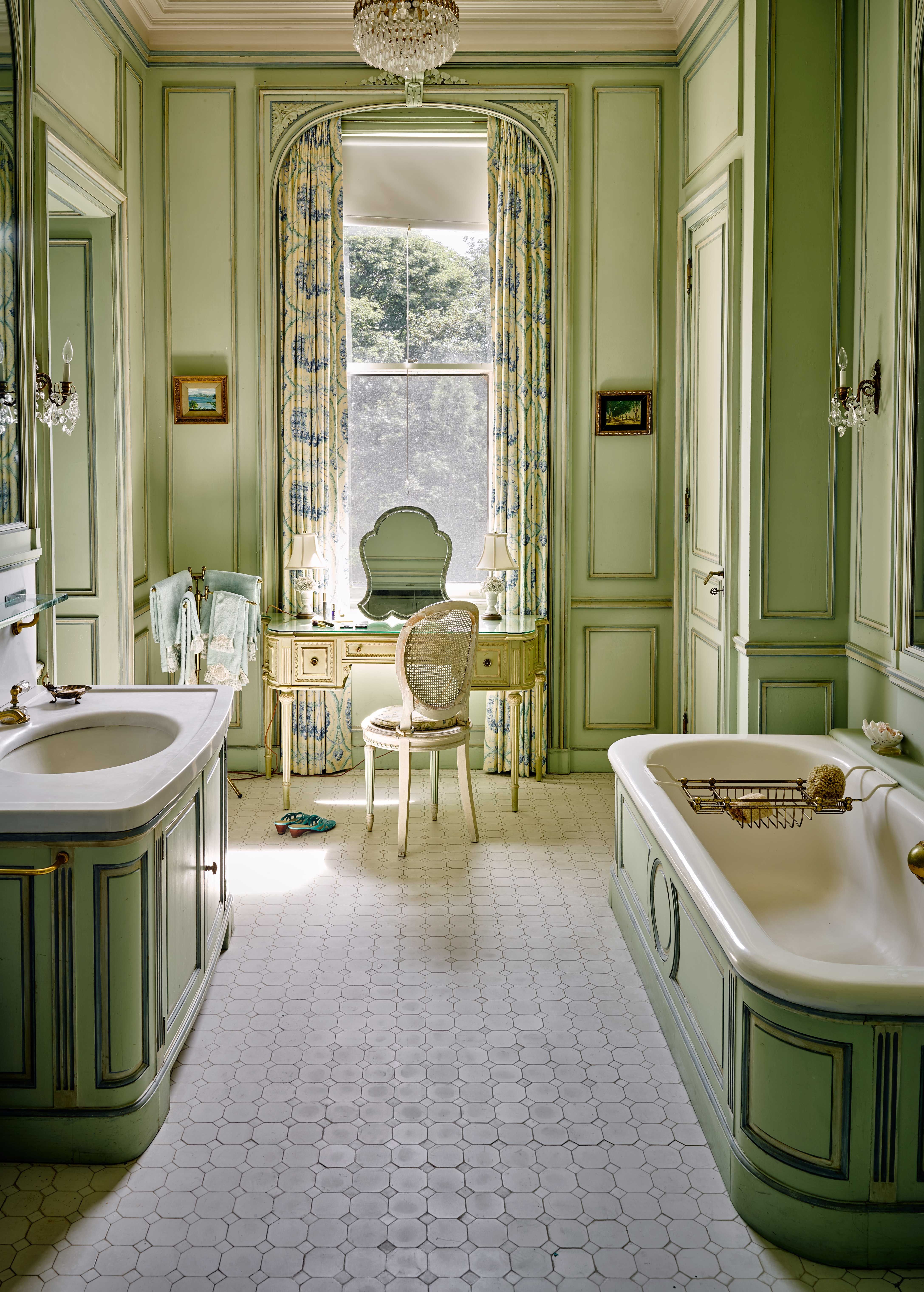 bathroom, white tiles, light green wall wainscoting, chandelier, white tub, green cabinet, make up table