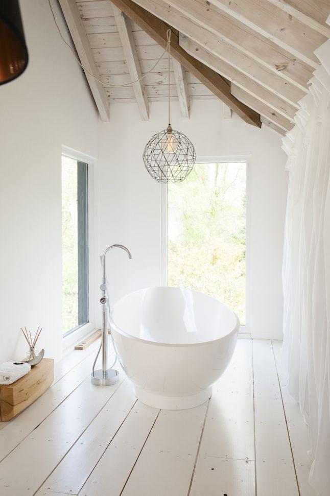bathroom, white wall, white floor, vaulted white wooden ceiling, black iron framed pendant, white tub