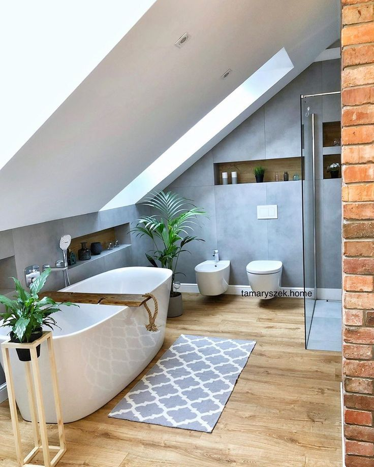 bathroom, wooden floor, grey wall, white vaulted ceiling, white tub, brick exposed wall