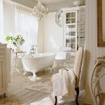 Bathroom, Wooden Floor, White Wooden Wall, Chandelier, White Tub Clawfoot, White Patterned Rug, White Chair, White Cabinet
