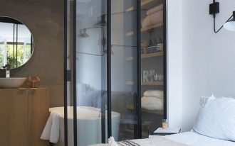 bathroom, wooden shelves, white tub, white sink, glass sliding door
