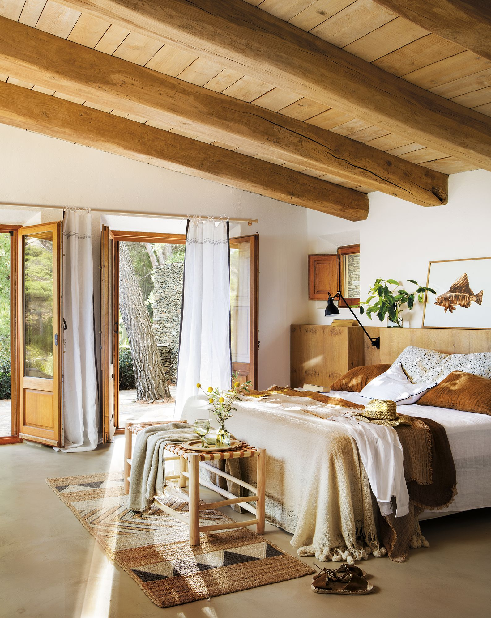 bedroom, brown floor, white wall, wooden headboard, white bed, wooen bench, wooden ceiling, wooden beams, black sconce, patterned rug