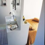 Bedroom, Grey Floor, White Wall, White Partition, White Vanity, Whit Sink, White Shelves, Yellow Bed