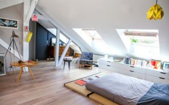 bedroom, wooden floor, white vaulted ceiling, ceiling windows, white cabinet, bed, round wooden coffee table