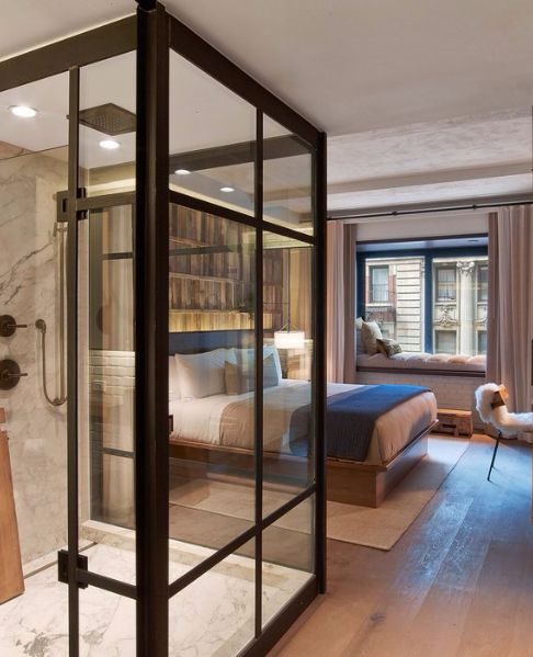bedroom, wooden floor, white wall, window nook, shelves, wooden bed platform, glass wall bathroom, marble wall and floor